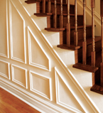 Oak staircase with white paneling along the side of the staircase