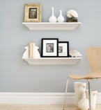 Light grey wall with two white boards on the wall and white moulding on the bottom of the wall