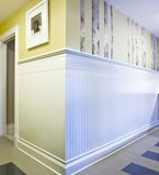 Yellow walls with wainscot half way up the wall with white baseboards